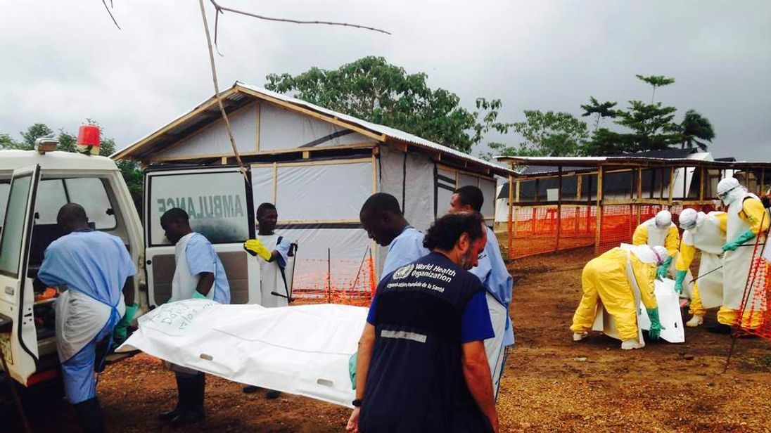 Volunteers carry bodies in a centre run by Medecins Sans Frontieres for Ebola patients in Kailahun