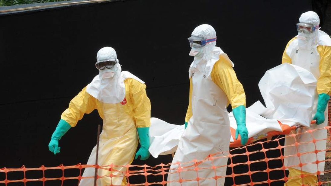 Staff carry the body of an ebola victim in Guinea