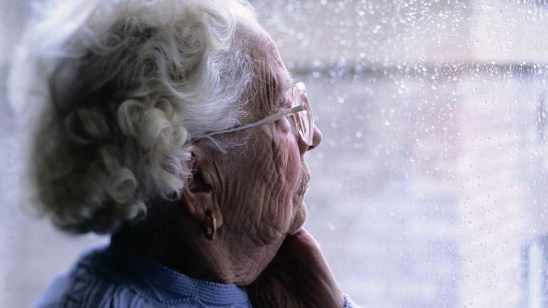 Elderly Woman Looking Out Of A Window