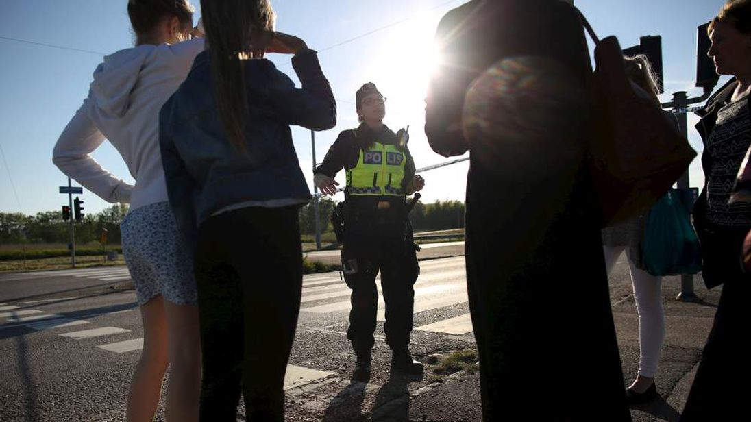 A police officer speaks to eyewitnesses after a car exploded (not pictured) at a roundabout in Gothenburg