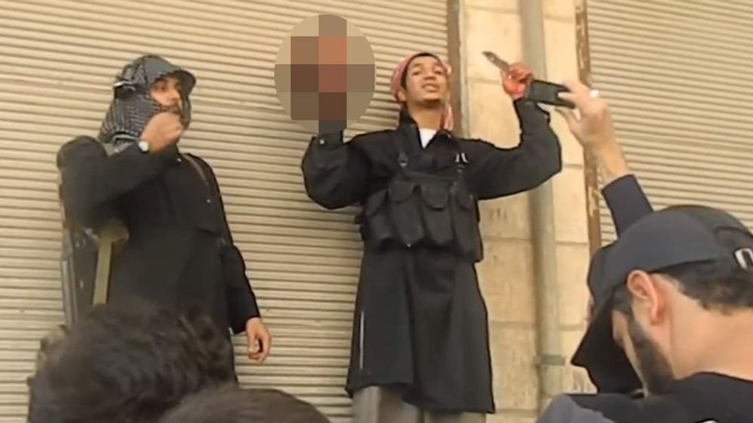 Video released show Al-Qaeda linked jihadists with the severed head of a wrongly accused and killed man in Syria