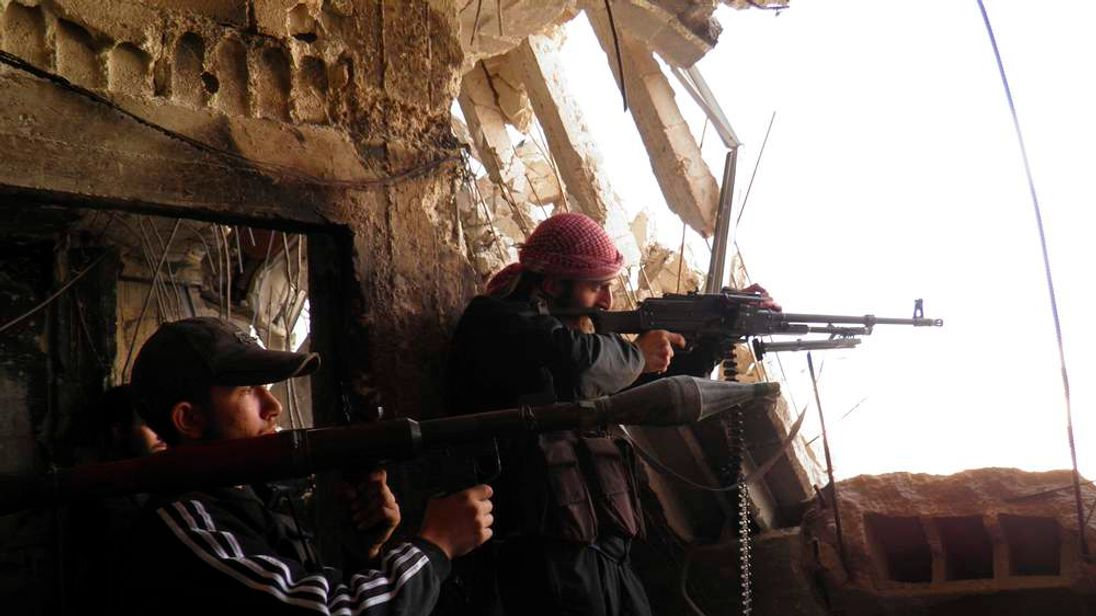 Free Syrian Army fighters with weapons stand guard at the frontline against forces loyal to Syrian President Bashar al-Assad in the Al-khalidiya neighbourhood of Homs