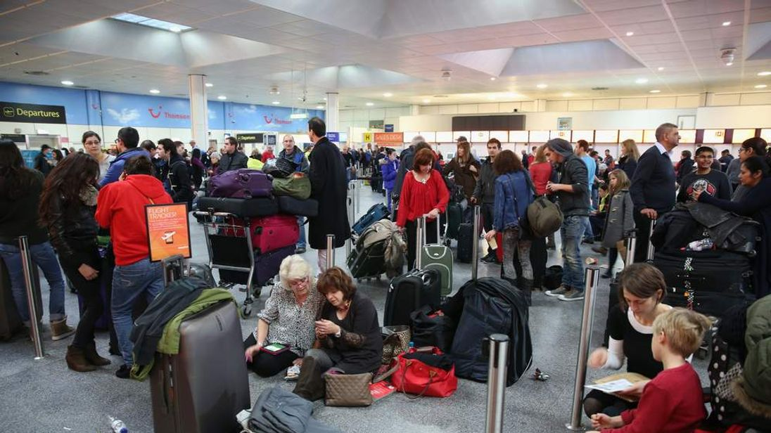 Passengers wait in the departure hall of Gatwick airport's North Terminal as severe weather causes delays and cancellations to numerous flights from the airport