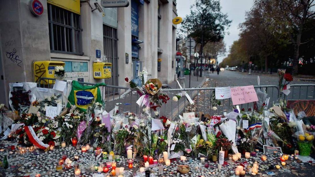 Flowers, candles and tributes cover the pavement near the scene of the Bataclan Theatre terrorist attack