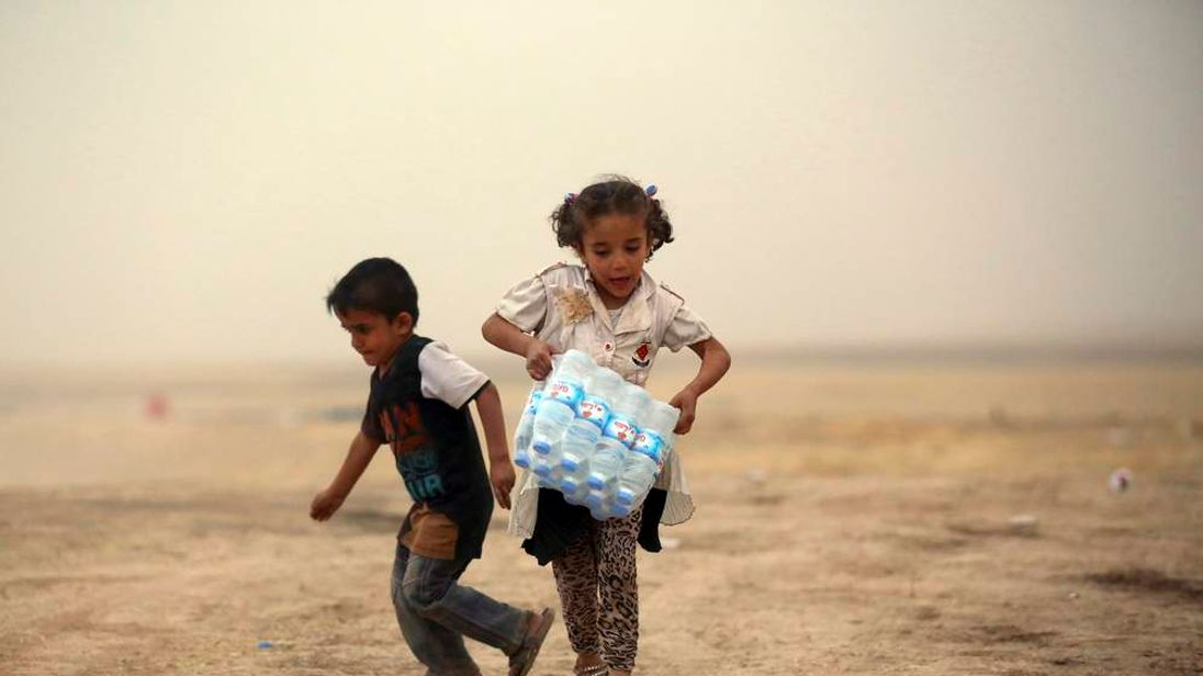 A girl who fled from the violence in Mosul carries a case of water at a camp on the outskirts of Arbil