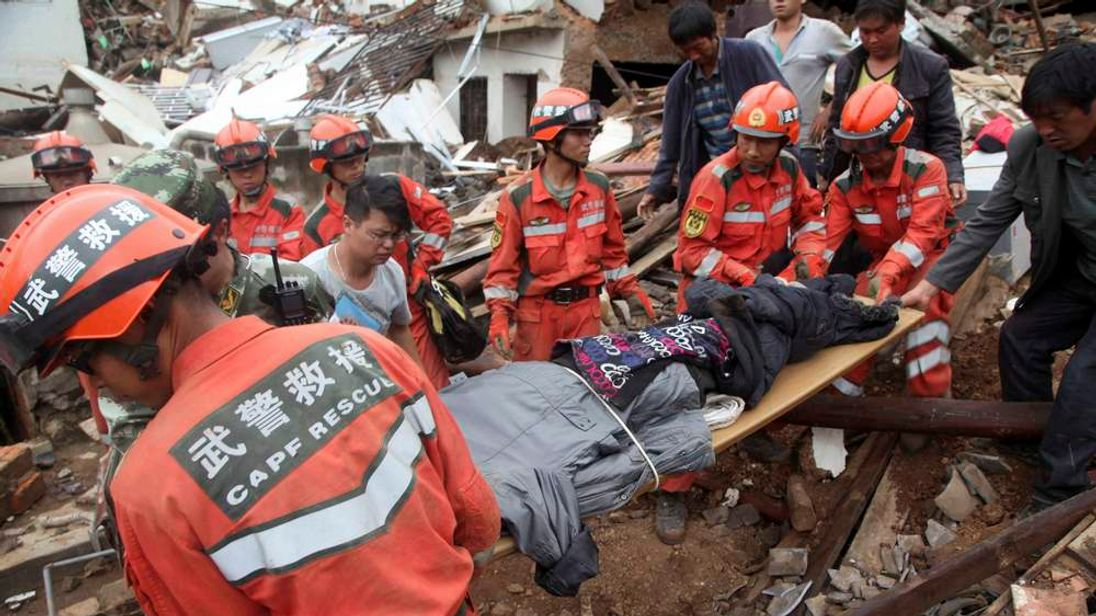 Rescue workers evacuate an injured person after a magnitude 6.3 earthquake hit Longtoushan town