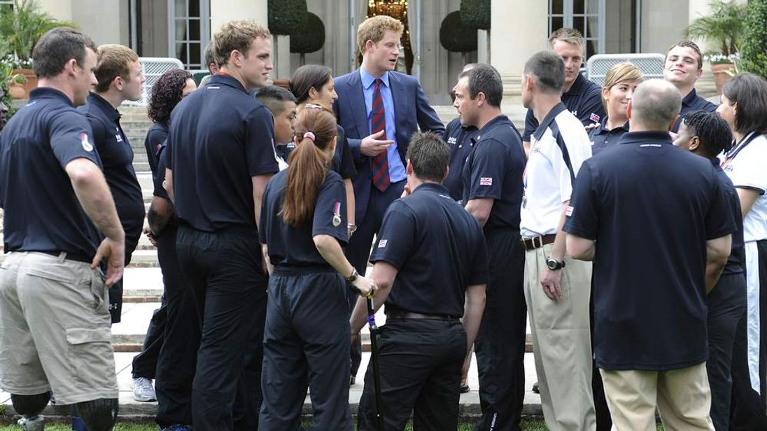 Prince Harry (TOP C) talks with wounded U.K. service members at the British Embassy