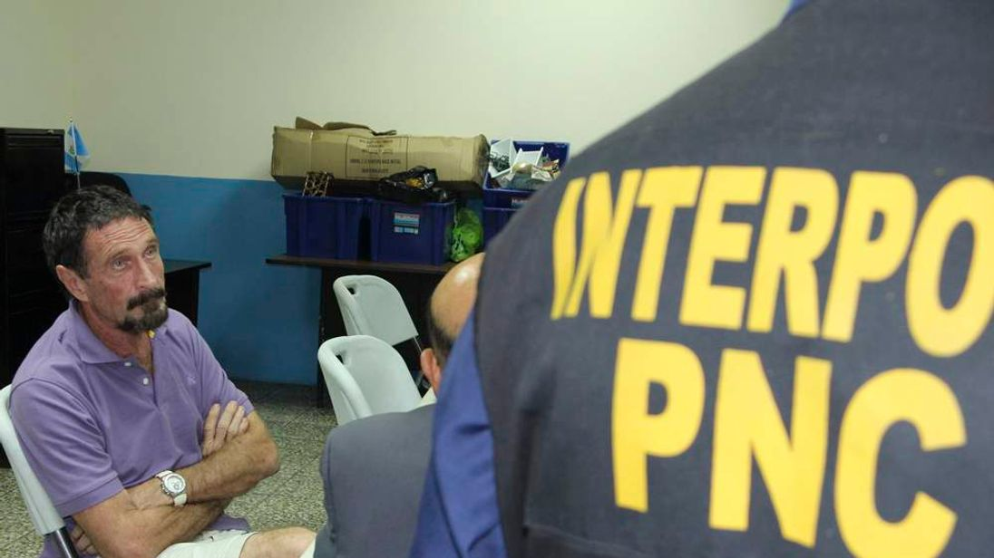 U.S. anti-virus software guru John McAfee sits next to an INTERPOL agent after his detention in Guatemala City