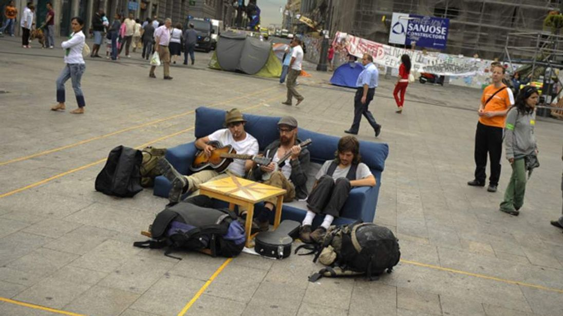Men sit on a couch and play guitar as protesters camp at the Puerta del Sol square in Madrid