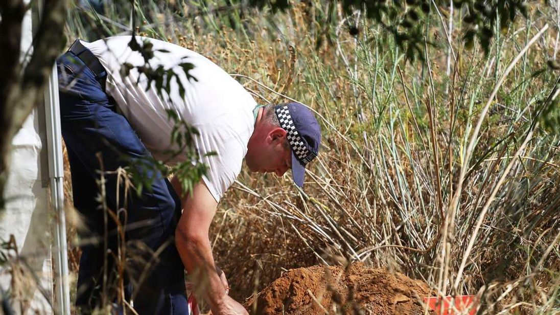 A British police officer checks soil samples dug from a hole in an area of wasteland
