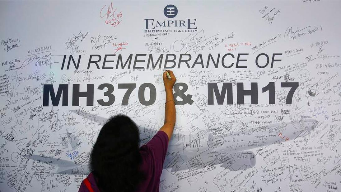 A woman writes a message on a dedication board for victims of the downed Malaysia Airlines Flight MH17 airliner and the missing Flight MH370, in Subang Jaya
