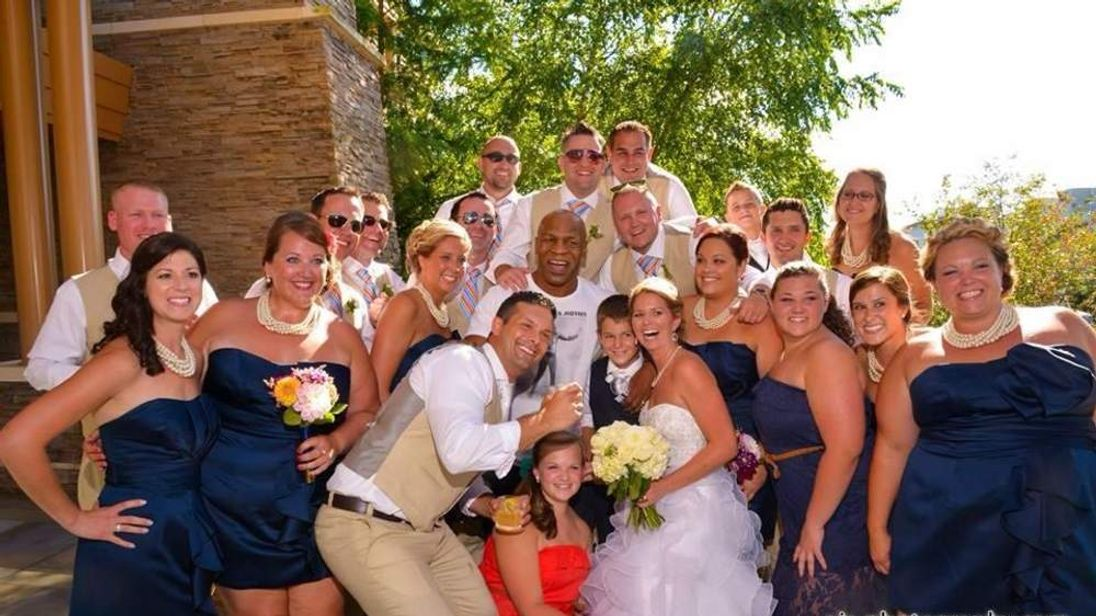 Mike Tyson poses for photographs with newlyweds
