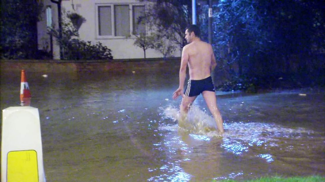 A resident braves the floods in St Asaph, north Wales