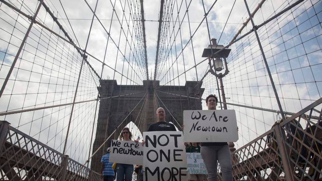 Demonstrators march across the Brooklyn Bridge in a protest calling for tougher gun control laws in New York