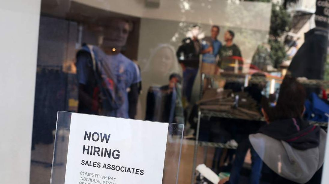 """A """"now hiring"""" sign is posted in the window of a store in San Francisco."""