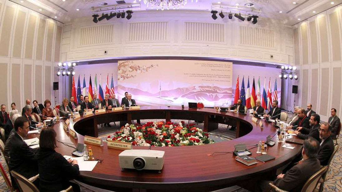 Participants sit at a table during talks on Iran's nuclear programme in Almaty