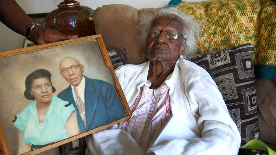 Talley sits on her couch, as a photograph showing her and her late husband Alfred is held next to her, on her 115th birthday in her home in Inkster