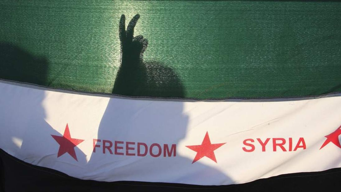 Protesters with a Syrian opposition flag