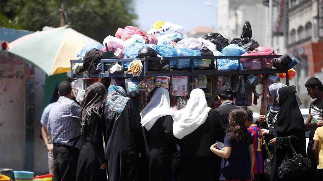 Palestinian residents shop on a street in Gaza City during a temporary five-hour humanitarian ceasefire observed by Israel and the Palestinian group Hamas