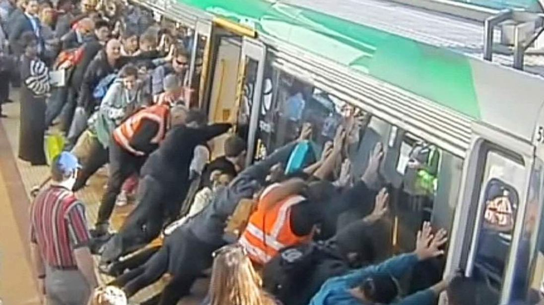 Passengers push to tilt a train to help free a trapped man