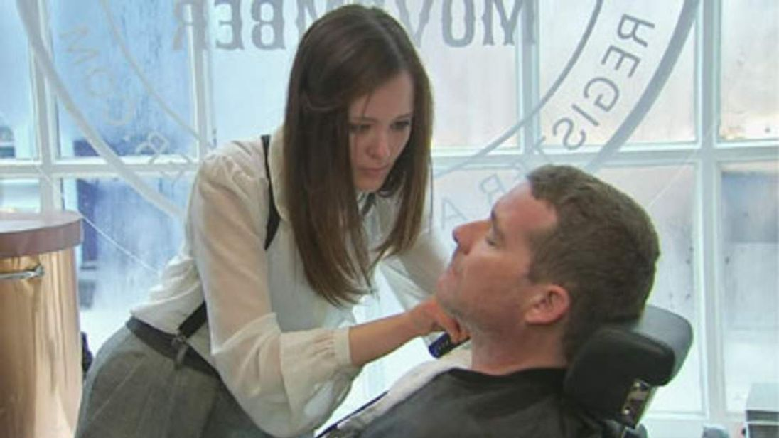 A man has his moustache shaved off in central London.