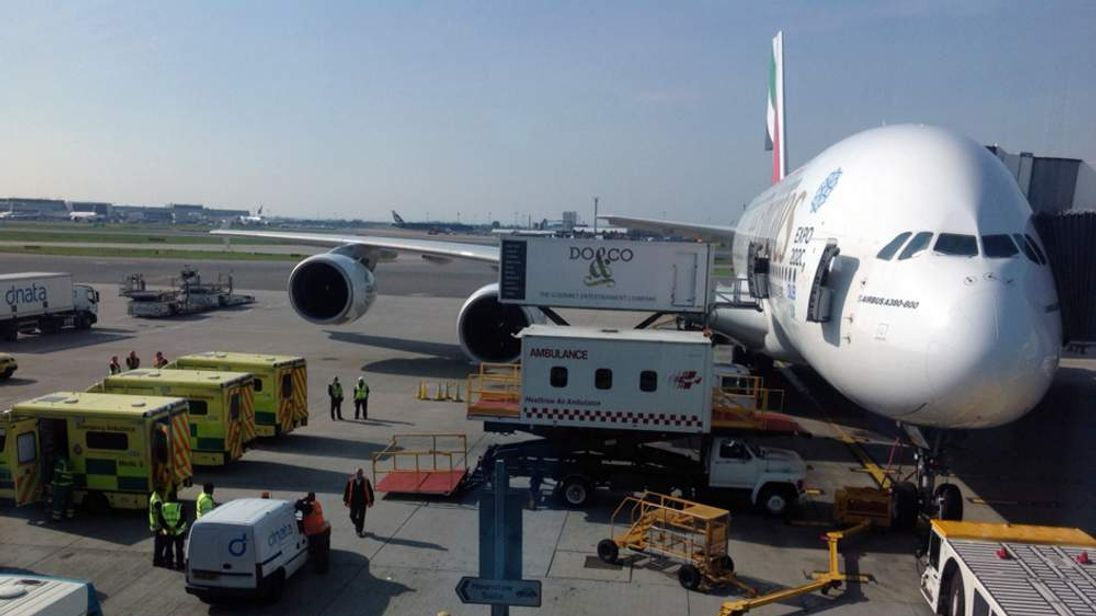 Children are treated by paramedics after falling ill on an Emirates flight to Heathrow