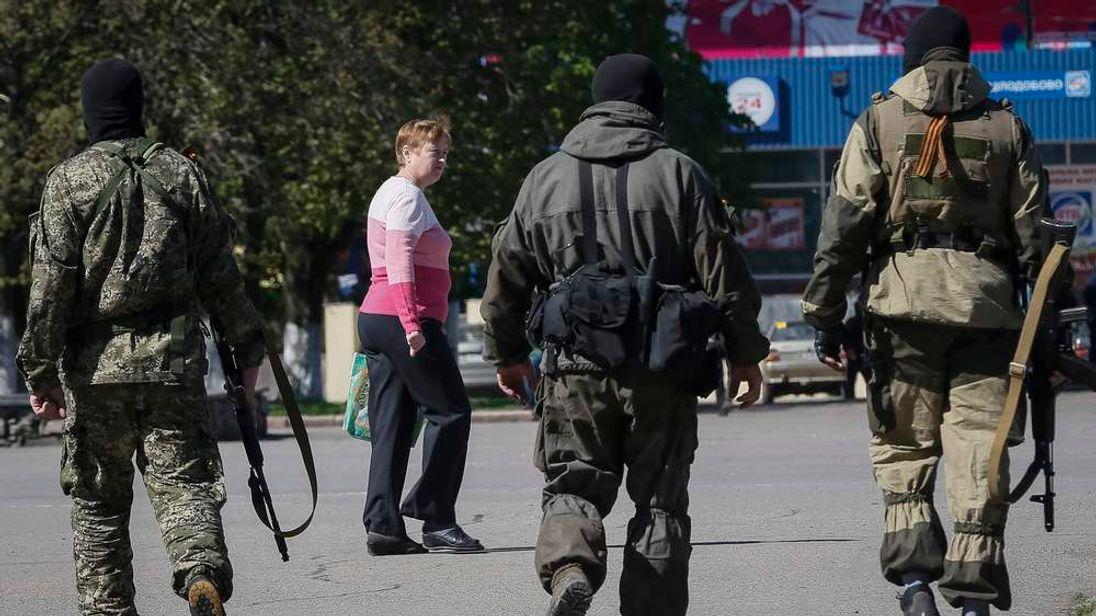 Pro-Russian armed men walk down a street in central Slaviansk