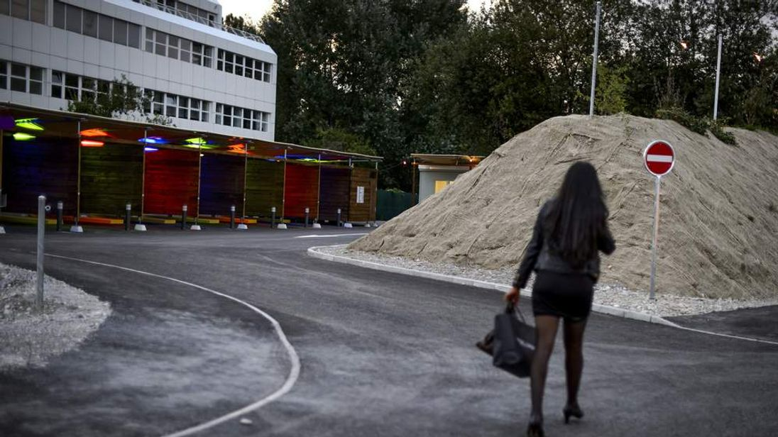 "A prostitute walks past so-called ""sex boxes"" at the opening day of Switzerland's first sex drive-in"