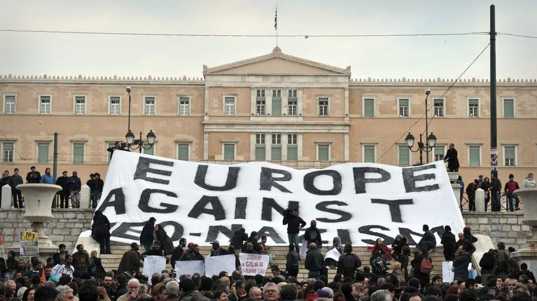 """Activists hold a banner, reading: """"Europe Against Neo-Nazism,"""" in front of the Greek Parliament in Athens"""