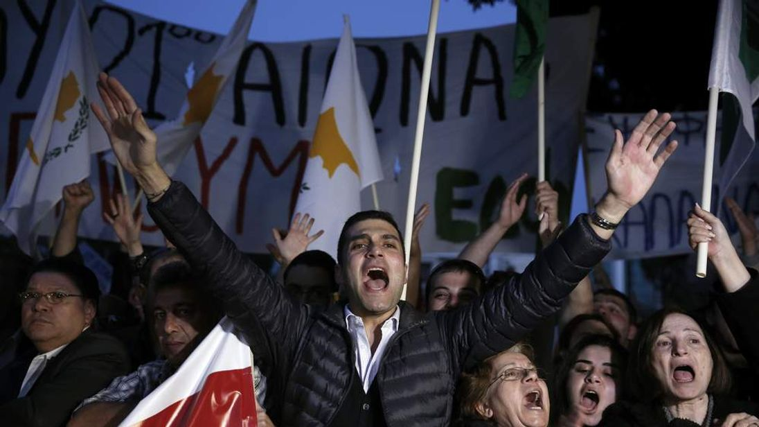 Protesters shout slogans during an anti-bailout rally outside Cyprus' parliament