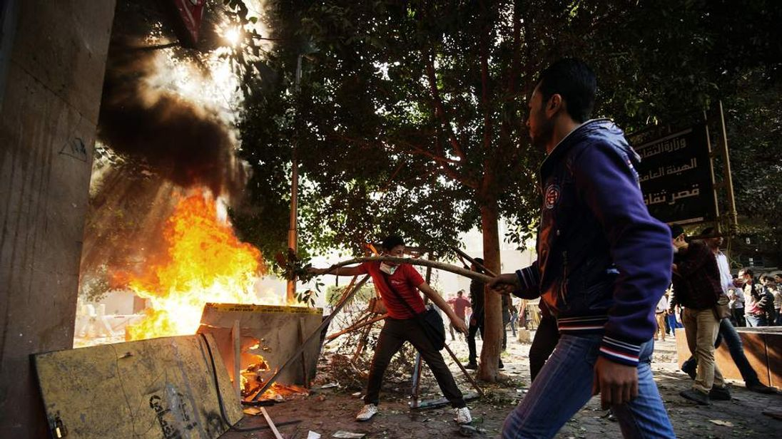 Protesters throw branches on a bonfire as they clash with Egyptian riot policemen