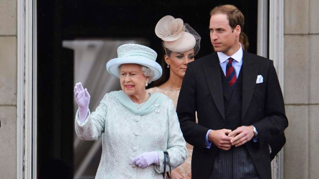 The Queen waves next to Prince William and the Duchess of Cambridge