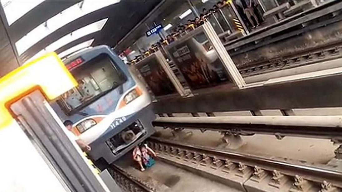 Pregnant woman's miraculous escape after falling onto track in front of train, Beijing, China - 01 Jul 2014