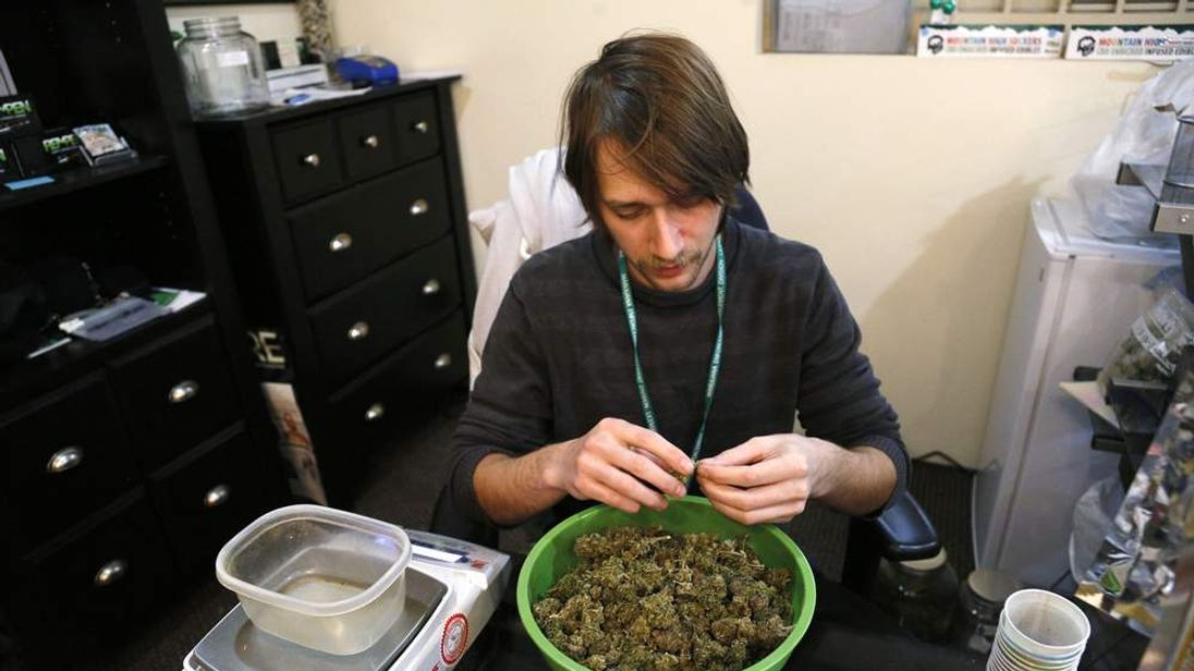 Skylar Hall prepares marijuana buds for sale at the Botanacare marijuana store