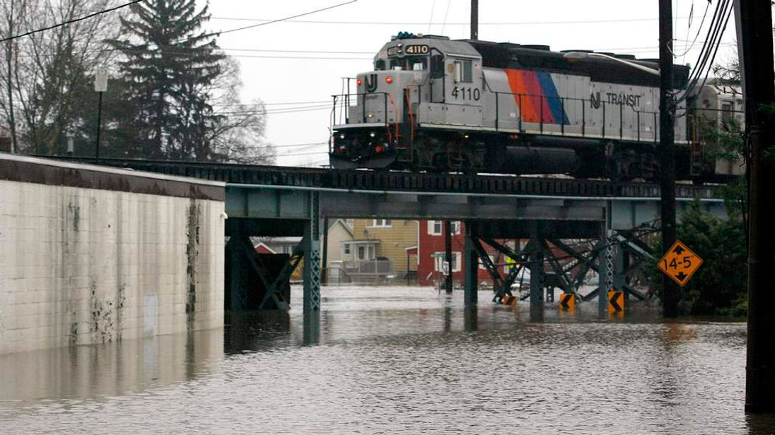 A NJ Transit commuter train travels over a flooded underpass in Garfield, New Jersey