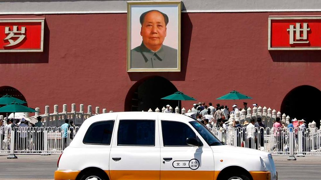An iconic 'London cab' drives past the giant portrait of Chairman Mao Zedong that hangs in Beijing's Tiananmen Square June 29, 2009 after Geely bought 20%