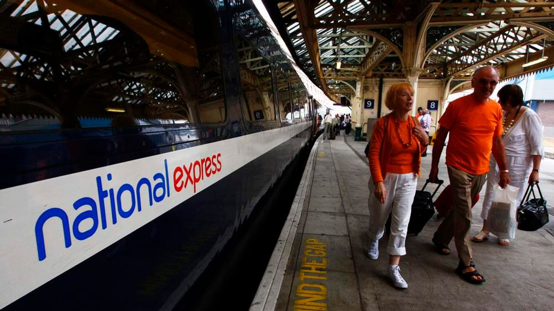 Passengers walk past a National Express East Coast line train at Waverley Station in Edinburgh, Scotland