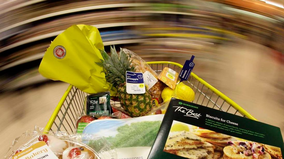 A shopping trolley is pushed around a Morrisons store