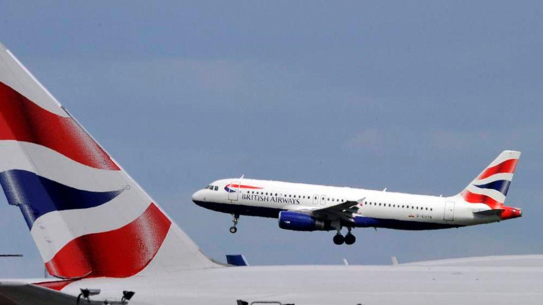 A British Airways plane flies intoHeathrow Airport in west London