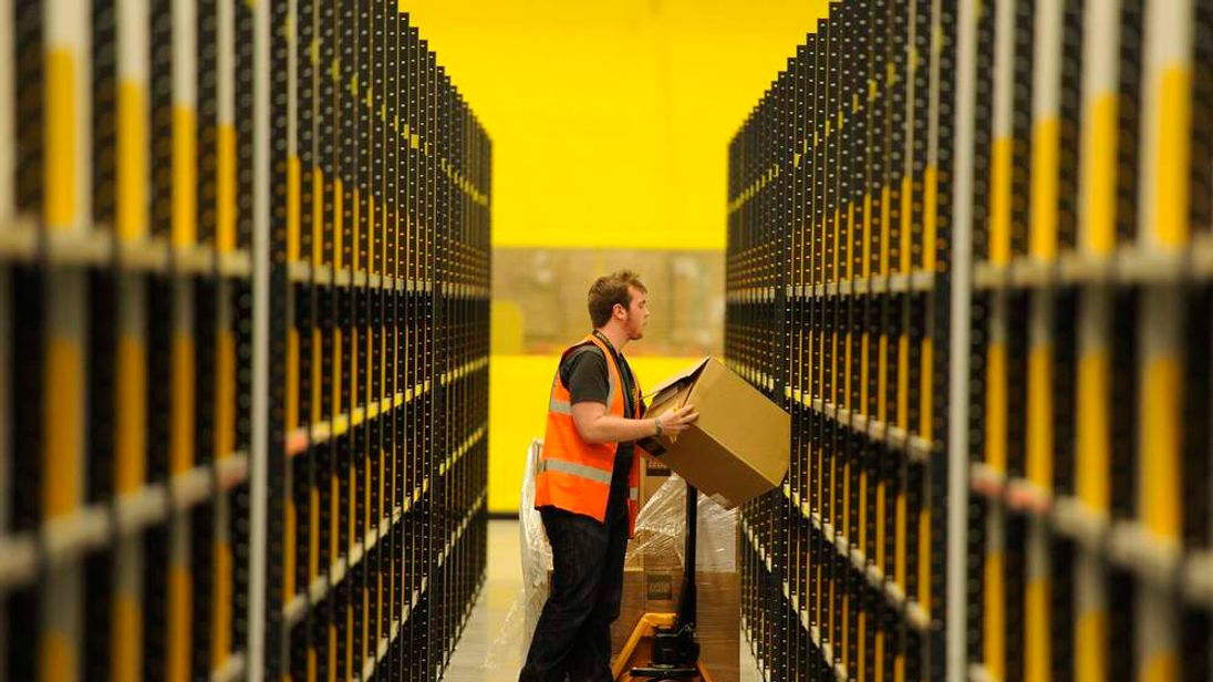 A worker lifts a box at Amazon's new fulfilment centre after it was opened by Scotland's First Minister Alex Salmond in Dunfermline, Scotland,