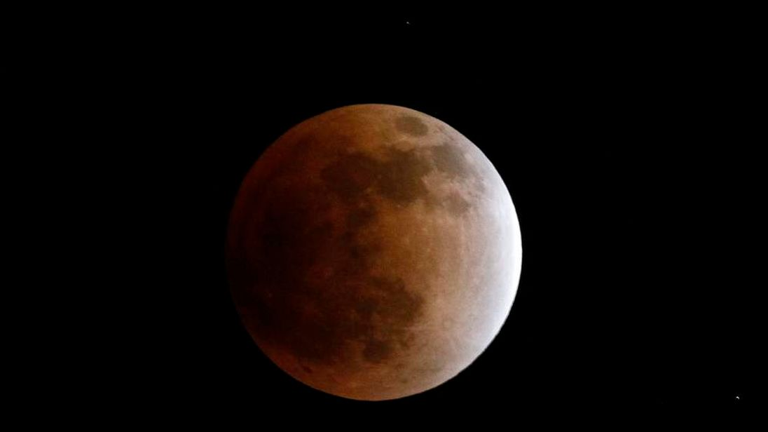 The earth's shadow falls on the moon as it emerges from a total lunar eclipse above Shanghai