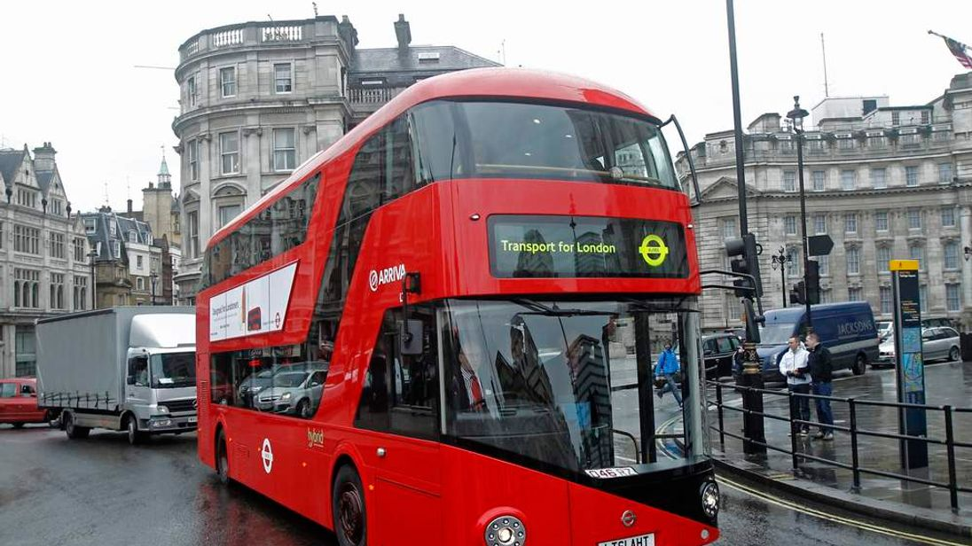 A prototype of a new style London bus circles Trafalgar Square in London