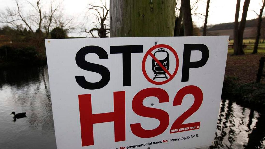 A duck swims past a HS2 protest sign in Little Missenden
