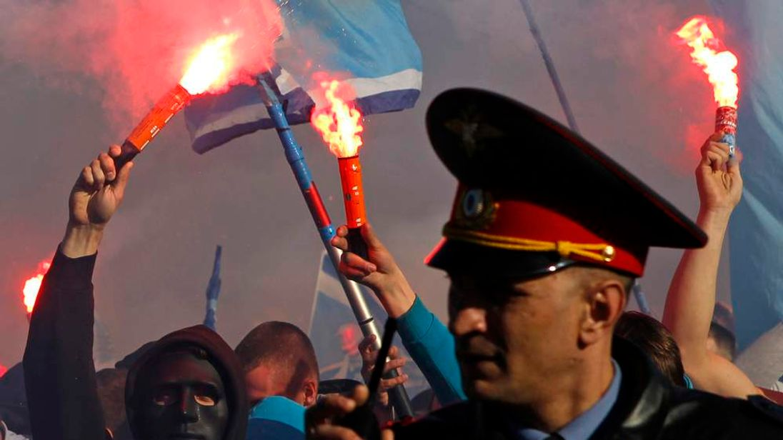 Zenit supporters light a flare near a Russian policeman before their team's their Premier league soccer match against Dinamo Moscow in St.Petersburg