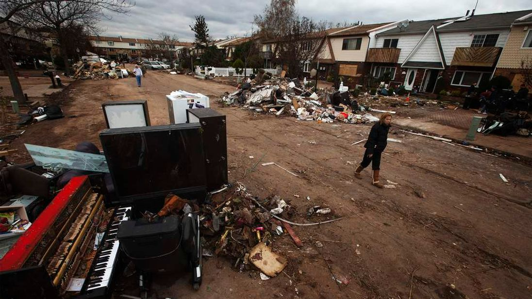 A woman surveys flood damaged personal property thrown into the streets in the New Dorp Beach neighborhood of the Staten Island borough of New York, November 1, 2012.