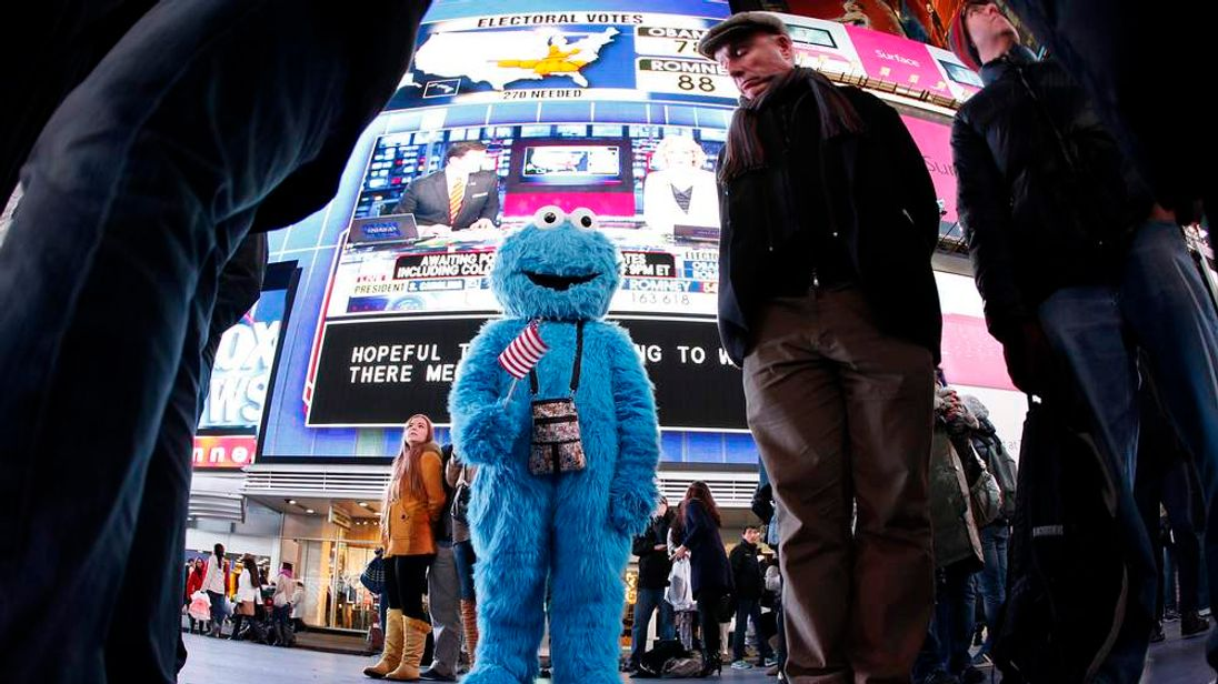 A man dressed as the character Cookie Monster watches TV screens in Times Square giving U.S presidential election results in New York