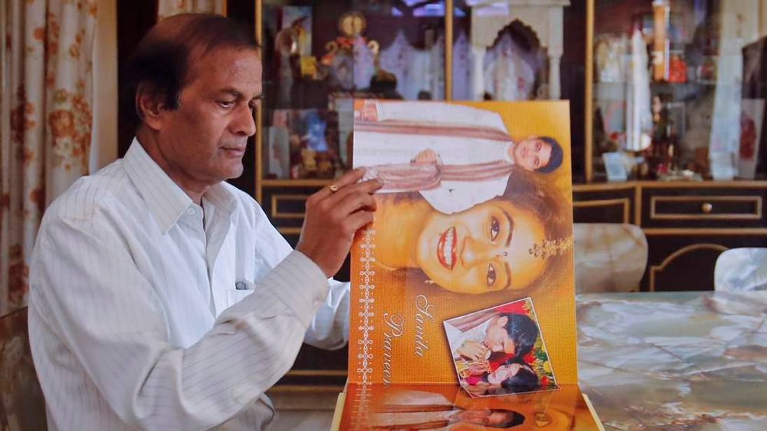 Andanappa Yalagi, the father of Savita Halappanavar, looks at her wedding album at her house in Belgaum in the southern Indian state of Karnataka November 16, 2012.