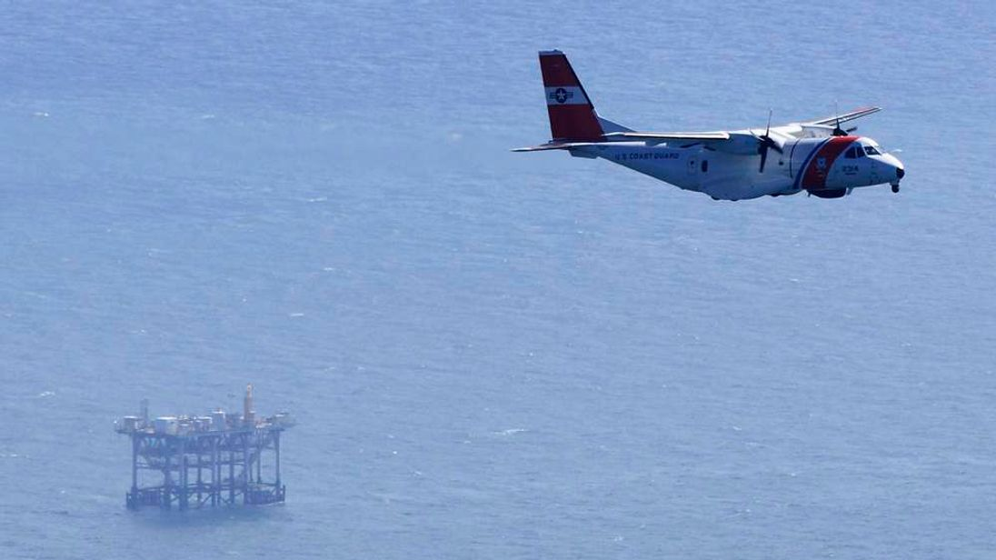 A plane from the U.S. Coast Guard flies near an oil platform which exploded early this morning in the Gulf of Mexico, off the coast of Louisiana, November 16, 2012.