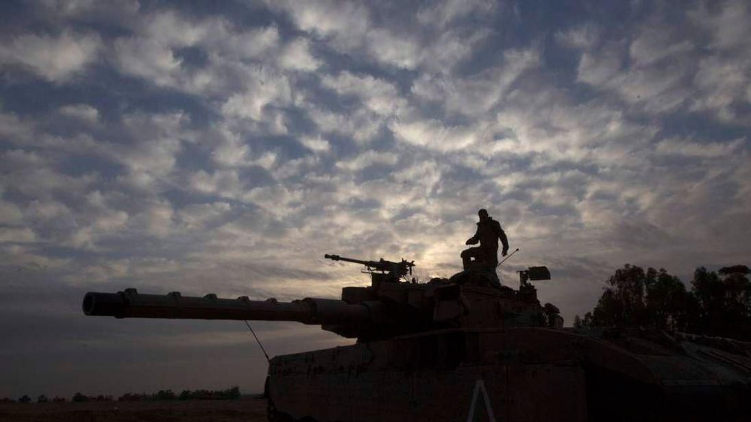 An Israeli soldier stands atop a tank near the border with the Gaza Strip November 17, 2012