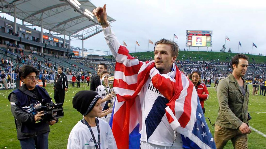 Los Angeles Galaxy's David Beckham gives a thumbs up to the crowd next to his son Romeo after Galaxy defeated the Houston Dynamo to win the MLS Cup championship soccer game in Carson